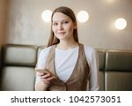 woman in office with mobile... | Shutterstock . vector #1042573051