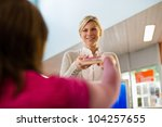 Portrait of young female college student returning book to librarian in public library - stock photo