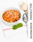 Small photo of Bowl of Minestrone, a traditional Italian low calorie vegetable soup made of carrots, peas, beans, celery, tomatoes, garlic and onions with grated parmesan cheese and basil on white kitchen table