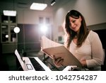 smiling woman reading music... | Shutterstock . vector #1042754287