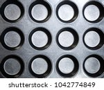 Small photo of Closeup unsaturated photograph of gray metal cupcake baking pan with round circular shape great for a background image, wallpaper or backdrop.