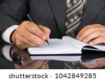 man in gray suit holds a metal... | Shutterstock . vector #1042849285