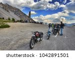 Small photo of Group of vintage motorbike rider layover front view in mountain landscape with cloudy sky France Alps Izoard hill pass circa June 2015