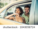 interracial couple driving on a ... | Shutterstock . vector #1043058724