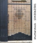 Small photo of Large Wooden door with traditional arabic studs and iron bars in Almeria, Spain