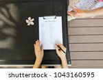 Small photo of sunlight portrait of woman fill visa application in travel agency. close up hands, pen and document. concept of private retailer or public service provides tourism related services on behalf of