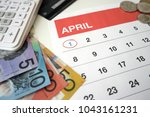 Small photo of April calendar with the first of the month highlighted and Australian dollar bills, coins, calculator, credit card in the background