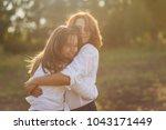 happy mother with her daughter... | Shutterstock . vector #1043171449
