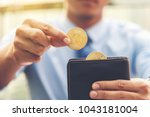 Small photo of Closed up on businessman right hand holding bitcoin, another half bitcoins on wallet left hand. Golden bitcoin coins in man's hands. Virtual currency. New virtual money.