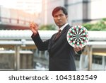 Small photo of Successful asian businessman hold arrow in hand at the city, achievement goal. Aim in business concept. Aspirational people. Mission achieved.