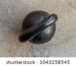 Small photo of Old rusty black kettlebell 16 kg pood on noncrete floor background top view