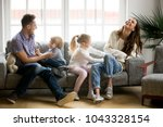 Small photo of Happy parents and kids having fun tickling sitting together on sofa, cheerful couple laughing playing game with little active children son and daughter in living room at home, family funny activity