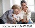 smiling mother taking selfie... | Shutterstock . vector #1043328181