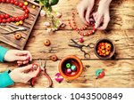 woman makes an ornament from... | Shutterstock . vector #1043500849