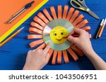 child makes smiling sun from cd.... | Shutterstock . vector #1043506951