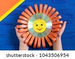 child makes smiling sun from cd.... | Shutterstock . vector #1043506954