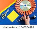 child makes smiling sun from cd.... | Shutterstock . vector #1043506981