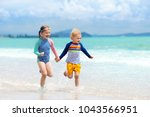 child playing on tropical beach.... | Shutterstock . vector #1043566951