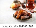 eid mubarak with  tea and dates.... | Shutterstock . vector #1043601187
