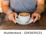 women holding a hot white cup... | Shutterstock . vector #1043654131