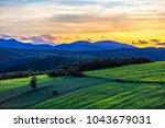 sunset landscape over the green ... | Shutterstock . vector #1043679031
