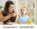 happy mom feeding her baby son... | Shutterstock . vector #1043683984