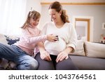 lovely excited pregnant mother... | Shutterstock . vector #1043764561
