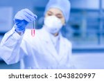 female scientist looking at the ... | Shutterstock . vector #1043820997