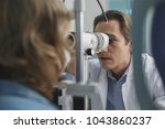 concentrated doctor examining... | Shutterstock . vector #1043860237