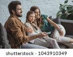 happy parents and daughter... | Shutterstock . vector #1043910349