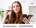 young woman applying make up... | Shutterstock . vector #1043930581