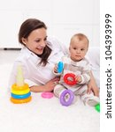Baby girl and mother playing on the floor with colorful items - stock photo