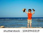 a little child on the beach... | Shutterstock . vector #1043943319