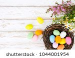 colorful easter eggs in nest... | Shutterstock . vector #1044001954