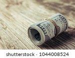 roll of one hundred dollars... | Shutterstock . vector #1044008524