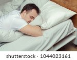 young man sleeping on bed in... | Shutterstock . vector #1044023161