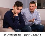 boy is offended and father is... | Shutterstock . vector #1044052645