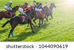 Stock photo race horses sprinting towards the finish line with sunlight lens flare effect 1044090619