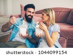modern young lazy couple eating ... | Shutterstock . vector #1044099154