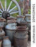 Old Milk Churns And A Old Wheel