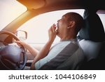 sleepy yawning man driving car... | Shutterstock . vector #1044106849