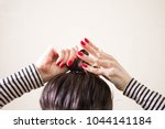 woman is doing her hair ... | Shutterstock . vector #1044141184