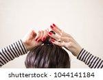 woman is doing her hair ... | Shutterstock . vector #1044141184