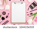 Small photo of Beauty composition with clipboard, tulips flowers, cosmetics and accessory on pink background. Top view. Flat lay. Home feminine desk.