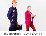 Small photo of Builder in helmet looks at woman with busy face counting money, isolated on white background. Customer deceives repairman, builder, mechanic. Repairer, builder wants salary for work. Deceive concept.
