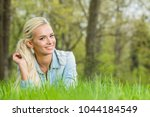 young blonde woman laying on... | Shutterstock . vector #1044184549