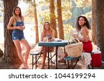 Three female friends hanging out by a lake smiling to camera - stock photo