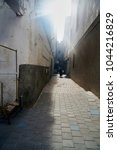 Small photo of The Medina of Essaouira (Old town), Morocco; November 08 2017; Local man walking through a narrow passage with colorful painted walls in the Medina of Essaouira (Old town), Morocco.