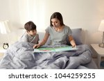 mother reading bedtime story to ...   Shutterstock . vector #1044259255