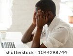 Small photo of African american businessman feeling headache migraine at work touching temples, stressed tired upset black man feeling dizzy or depressed and frustrated while working on laptop in office, side view
